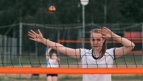 Het professionele volleyball dient vrouw op de strandtoernooien Netto het volleyball de speler blokkeert de mening wanneer het in stock videobeelden