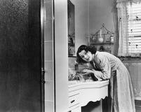 Het profiel van een jonge vrouw die haar wassen dient de badkamersgootsteen in (Alle afgeschilderde personen leven niet langer en stock afbeeldingen