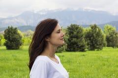 Het profiel van jonge vrouw met ogen sloot ademhalings verse lucht in de bergen stock afbeeldingen