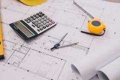 Het project van het architectenbureau in bouwwerf met blauwdruk, pen, t royalty-vrije stock foto