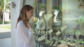 Het Prtettymeisje kiest juwelen in winkelvenster tijdens het winkelen stock video
