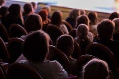 Het publiek in het theater die op een spel letten Het publiek in de zaal: volwassenen en kinderen stock foto