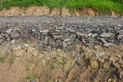 Het puin van het asfalt op de grond waar het gras. Stock Foto's