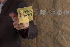Het punt van de zakenmanhand het creatieve denken op kleverige nota met ico Royalty-vrije Stock Afbeeldingen