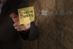 Het punt van de zakenmanhand het creatieve denken op kleverige nota met ico Stock Afbeelding