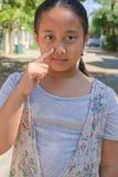 Het punt van het meisje haar vinger aan wang en dichtbijgelegen neus Stock Foto