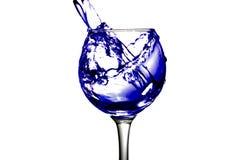 Het purpere water giet in een glas op een witte achtergrond Royalty-vrije Stock Afbeelding