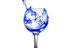 Het purpere water giet in een glas op een witte achtergrond Royalty-vrije Stock Foto's