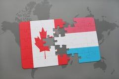 het raadsel met de nationale vlag van Canada en Luxemburg op een wereld brengen achtergrond in kaart Stock Afbeeldingen