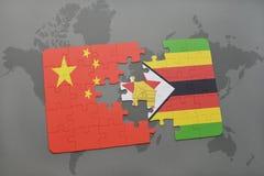 het raadsel met de nationale vlag van China en Zimbabwe op een wereld brengen achtergrond in kaart Royalty-vrije Stock Foto's