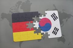 het raadsel met de nationale vlag van Duitsland en Zuid-Korea op een wereld brengen achtergrond in kaart Stock Foto