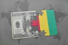 het raadsel met de nationale vlag van Guinea en het dollarbankbiljet op een wereld brengen achtergrond in kaart Royalty-vrije Stock Afbeeldingen