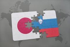 het raadsel met de nationale vlag van Japan en Slovenië op een wereld brengen achtergrond in kaart Stock Foto