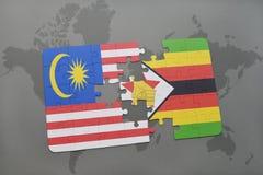 het raadsel met de nationale vlag van Maleisië en Zimbabwe op een wereld brengen achtergrond in kaart Stock Afbeeldingen