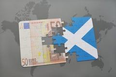 het raadsel met de nationale vlag van Schotland en het euro bankbiljet op een wereld brengen achtergrond in kaart Stock Foto's