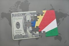 het raadsel met de nationale vlag van Seychellen en het dollarbankbiljet op een wereld brengen achtergrond in kaart Stock Foto