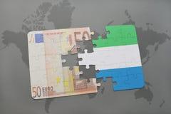 het raadsel met de nationale vlag van Sierra Leone en het euro bankbiljet op een wereld brengen achtergrond in kaart Royalty-vrije Stock Foto's