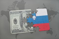 het raadsel met de nationale vlag van Slovenië en het dollarbankbiljet op een wereld brengen achtergrond in kaart Stock Foto