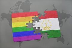 het raadsel met de nationale vlag van tajikistan en vrolijke regenboogvlag op een wereld brengt achtergrond in kaart Royalty-vrije Stock Foto