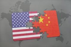 Het raadsel met de nationale vlag van de Verenigde Staten van Amerika en China op een wereld brengen achtergrond in kaart stock foto's