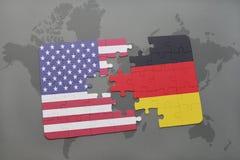 Het raadsel met de nationale vlag van de Verenigde Staten van Amerika en Duitsland op een wereld brengen achtergrond in kaart Stock Afbeeldingen