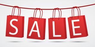 Het realistische rode winkelen doet het hangen op kabel met tekstverkoop op in zakken grijze achtergrond Stock Afbeeldingen
