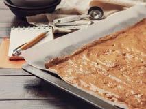 Het recept voor het koken van eigengemaakte cakes op de bodem van het bakseldienblad op houten achtergrond stock fotografie