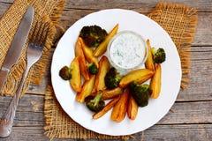 Het receptenidee van braadstukgroenten De oven roosterde aardappelsplakken en broccoli op een witte plaat, zure roomsaus Royalty-vrije Stock Afbeelding