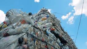 Het recycling van installatie met veel huisvuil Plastic die omslagen en flessen in stapels voor recycling worden gedrukt stock video