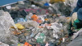 Het recyclingsinstallatie van het afval De arbeider van een huisvuil recyclingsfabriek neemt ongeschikte draagstoel van de transp stock videobeelden