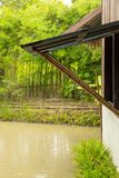 Het regenende venster open, gebruikend bamboepolen aan steun stroomt in p stock afbeeldingen