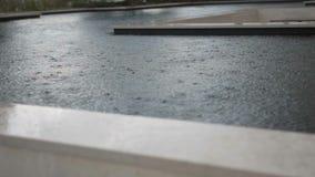 Het regent buiten Regendruppelsval in het water Langzame Motie Sluit omhoog stock videobeelden