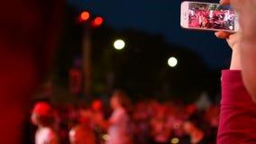 Het registreren van een video met mobiele telefooniphone tijdens de prestatiesoverleg van de popgroepmuziek op stadium stock footage