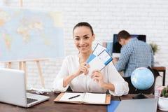 Het reisbureau houdt kaartjes voor het vliegtuig in het reisbureau Stock Foto