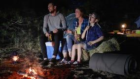 Het reiskamp van Amerikaanse familie in bos, ouders drinkt bier en het kind eet zefier dichtbij vuur in reis met tenten, stock videobeelden
