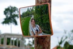 Het reizen in de rijstterras van Bali Kaukasische vrouwenglimlach in wegspiegel Stock Foto