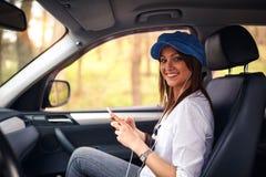 Het reizen door auto - Vrouw die op wegreis genieten van die aan luisteren Stock Afbeelding
