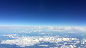 Het reizen door de lucht Mening door een vliegtuigvenster Blauwe hemel met wolken het vliegen Zonnig dagweer stock videobeelden