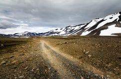 Het reizen onderaan een grintweg in sneeuwbergen van IJsland royalty-vrije stock foto's