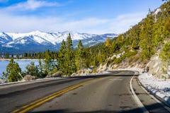 Het reizen op de oever van Meer Tahoe op een de winterdag; Siërra bergen met sneeuw zichtbaar op de achtergrond worden behandeld  stock fotografie