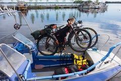 Het reizen van fietsen bond veilig aan een vissersboot op meer Saimaa, Finland stock foto's