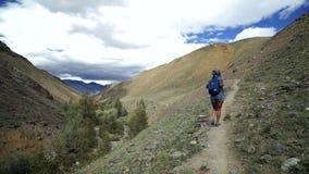 Het reizigersmeisje beklimt op steenberg Er zijn mooie berg en hemel met wolk op de achtergrond stock videobeelden