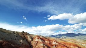 Het reizigersmeisje in hoeden zit op de rand van een rode berg Er zijn toneellandschap en bewolkte hemel op de achtergrond stock video