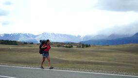 Het reizigersmeisje met een rugzak loopt aan de kant van de bergweg Er zijn sneeuwbergen op de achtergrond stock videobeelden