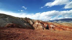 Het reizigersmeisje zit op de rand van een rode berg Er zijn toneellandschap en bewolkte hemel op de achtergrond stock videobeelden