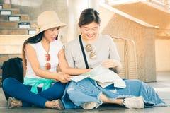 Het reizigerspaar met rugzakken zit op vloer samen gebruikend generische lokale kaart op zonnige dag royalty-vrije stock foto's