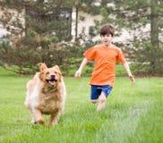 Het Rennen van de hond en van de Jongen Stock Fotografie