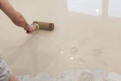 Het reparatiewerk Gietende vloeren in de ruimte Vul screed vloerreparatie en lever De arbeider richt cement op rol royalty-vrije stock fotografie