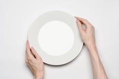 Het restaurant en het Voedsel als thema hebben: de menselijke hand toont gebaar op een lege witte plaat op een witte achtergrond  Royalty-vrije Stock Afbeelding