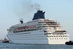 Het reusachtige cruiseschip verlaat de havenstad met behulp van zeesleepboot Stock Fotografie